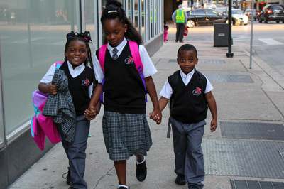 Image of three Pegasus students walking hand in and on the sidewalk.