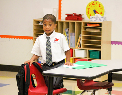 Image of a Pegasus student standing next to a red chair and white table.