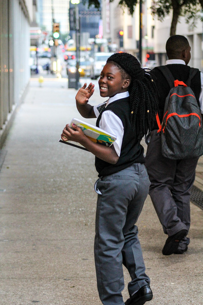 Image of a Pegasus student turning and waving as she walks down the sidewalk.