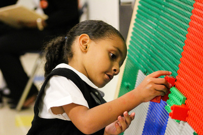 Image of a young Pegasus student performing an activity at a pegboard.